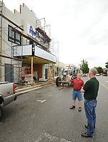 NWA Democrat-Gazette/ANDY SHUPE<br /> The Apollo on Emma owner Tom Lundstrum (right) speaks Friday, Aug. 11, 2017, with Terry Mason, owner of Mason's Old Time Barber Shop as workers continue to put the finishing touches on the building on Emma Avenue in Springdale. The event space plans to open Thursday.