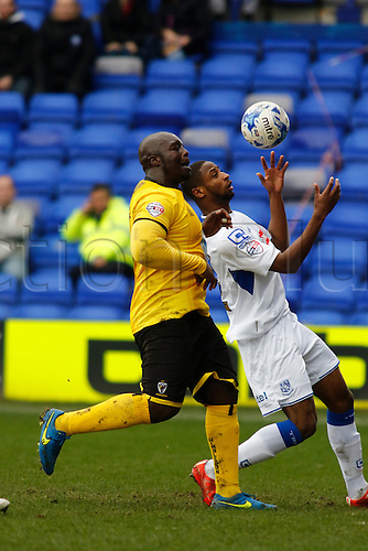 28.03.2015.  Tranmere, England. Skybox League 2. Tranmere Rovers versus AFC Wimbledon. AFC Wimbledon forward Adebayo Akinfenwa challenges Tranmere Rovers defender Janoi Donacien.