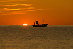 Fisherman in his small  boat silhouetted by rising sun on the horizon.