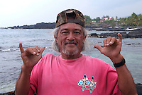 Native man making Hawaiian sign at remote village of Milolii South of Big Island Hawaii