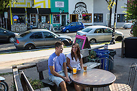 Young romantic couple spending time at outdoor patio bar on East 6th Street in East Austin Entertainment District, Austin, Texas.