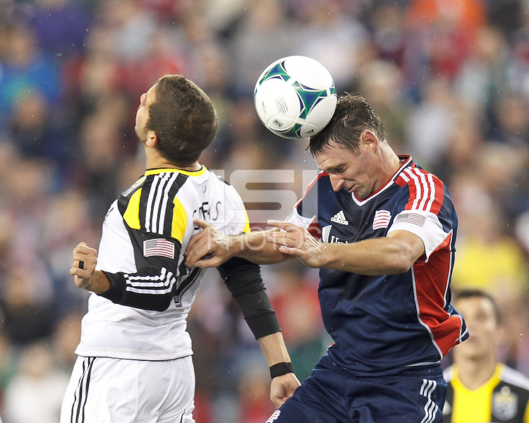 Columbus Crew substitute midfielder Ben Speas (17) and New England Revolution midfielder Andy Dorman (12) battle for head ball.  In a Major League Soccer (MLS) match, the New England Revolution (blue) defeated Columbus Crew (white), 3-2, at Gillette Stadium on October 19, 2013.