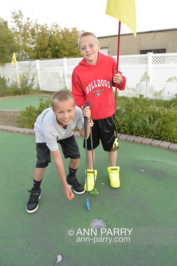 Freeport, New York, U.S. September 6, 2013. Brothers PAUL T, 11, in red top, and MATT T, 11, in gray top, visiting family in Long Island, play miniature golf at Crow's Nest Mini Golf at the Nautical Mile.