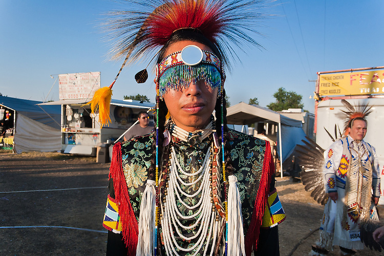 A dancer pauses for a portrait just outside the dancing arbor as he waits for his dance to be called.