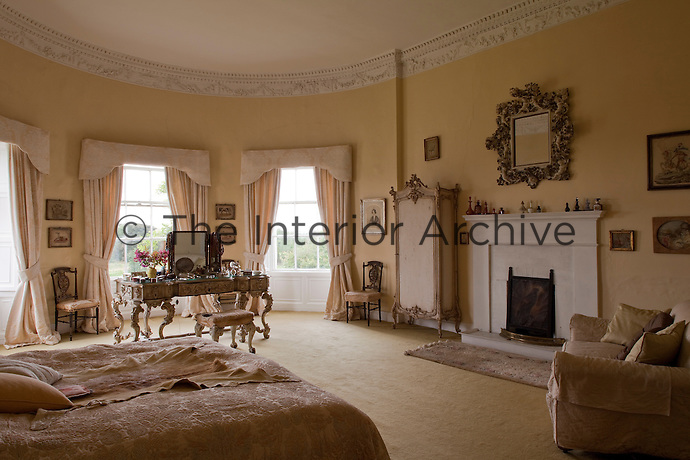 The oval shape of the master bedroom is punctuated by a magnificent dressing table in front of three graceful windows