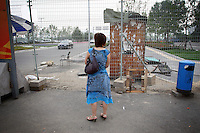 """CHINA. Beijing. A woman looks through a fence, trying to catch a glimpse of the new Olympic park. In recent years construction has boomed in Beijing as a result of the country's widespread economic growth and the awarding of the 2008 Summer Olympics to the city. For Beijing's residents however, it seems as their city is continually under construction with old neighborhoods regularly being razed and new apartments, office blocks and sports venues appearing in their place. A new Beijing has been promised to the people to act as a showcase to the world for the 'new' China. Beijing's residents have been waiting for this promised change for years and are still waiting, asking the question """"Where's the new Beijing?!"""". 2008."""