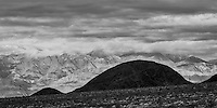 Layers of mountains and differing landscape textures in Death Valley during a clearing storm.