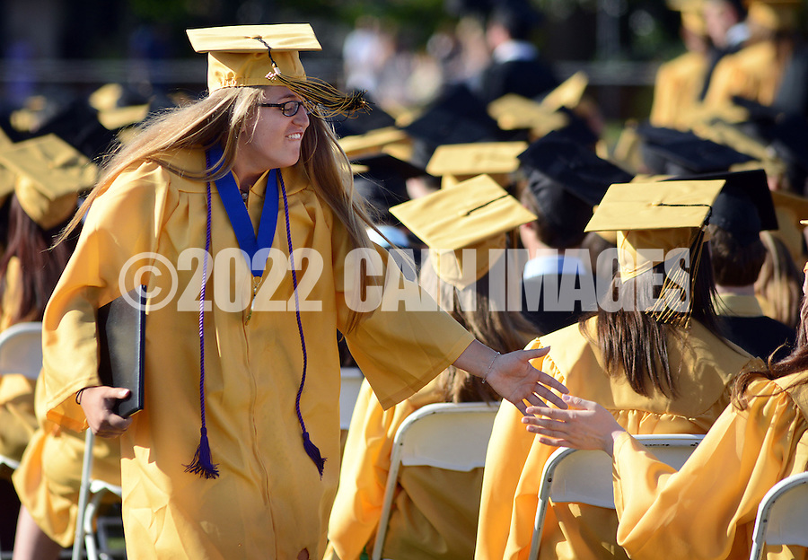 DOYLESTOWN, PA - JUNE 20: Graduate Elena Romesburg low fives a fellow graduate after receiving her diploma during Central Bucks West High School's commencement ceremony June 20, 2014 at the War Memorial Field in Doylestown, Pennsylvania.  (Photo by William Thomas Cain/Cain Images)