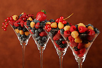 Agriculture - Mixed berries in a row of dessert glasses; strawberries, red & golden raspberries, blackberries, blueberries and red currants.