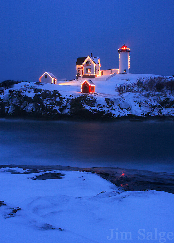 A snowstorm during the magical blue hour sets the mood at Nubble Lighthouse in Maine during the Holiday Season.