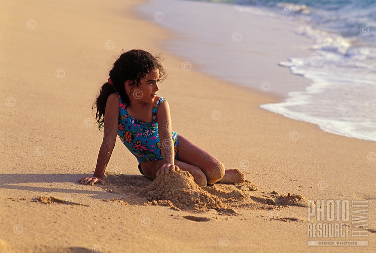 Young girl on sand near shoreline, north shore, Oahu.