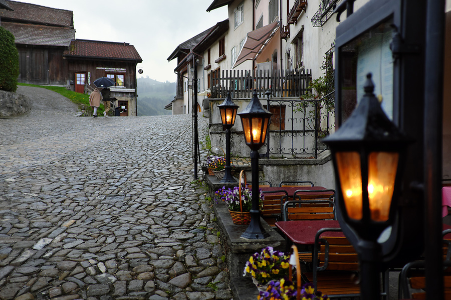 Lamps along side cobblestone street, Gruyères, Switzerland, Europe