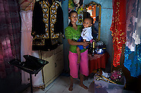 29 year old Irmayanti Wulandiri with her four year old daughter Lolita in their rented home. Irmayanti is a former student of the Kartini Emergency School and her daughter is currently in the kindergarten. Irmayanti was one of the first students trained by the 'Twin Teachers' as a wedding dresser, and after graduating the twins gave her a set of Javanese bride and groom outfits and make-up tools in order to kick-start her business. Since the early 1990s, twin sisters Sri Rosyati (known as Rossy) and Sri Irianingsih (known as Rian) have used their family inheritance to set up and run 64 schools in different parts of Indonesia, providing primary education combined with practical skills to some of the country's most deprived children. .