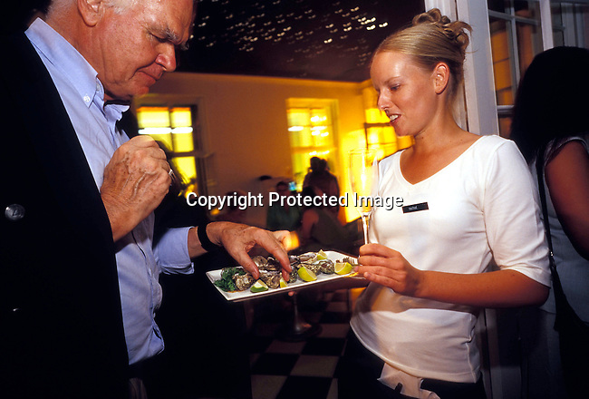 dipplei00180 .Crowd, rich, money, old, society, opening, man, waiter, oysters, seafood, plate. Unidentified up-market people gathered for the opening of a new bar at Mount Nelson Hotel in February, 2004 in Cape Town, South Africa..©Per-Anders Pettersson/iAfrika Photos