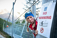 Runner with sad face at a no running sign on the world's longest suspension bridge, the Europaweg Bridge, while on the Via Valais, a multi-day trail running tour connecting Verbier with Zermatt, Switzerland.