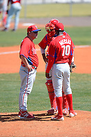 Philadelphia Phillies pitching coach Aaron Fultz (46) talks with pitcher Yoel Mecias (70) as catcher Gabriel Lino listens in during a minor league Spring Training game against the Atlanta Braves at Al Lang Field on March 14, 2013 in St. Petersburg, Florida.  (Mike Janes/Four Seam Images)