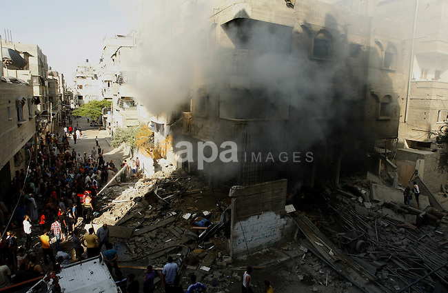 Members of civil defence and another man try to extinguish a fire caused after what police said was an Israeli air strike on a house, in Gaza City July 10, 2014. Israel pressed on with a punishing aerial offensive in Gaza for a third day on Thursday, killing eight members of a family including five children in a predawn strike, Palestinian officials said, while militants fired rockets at Israeli cities. The Israeli military had no immediate comment on the deadliest single bombing raid since the start of the offensive on Tuesday. The attack destroyed at least two homes in Khan Younis in southern Gaza, killing the eight people, the Palestinian Health Ministry said. Sixty-one Palestinians have been killed in the violence, more than 50 of them civilians, Palestinian medical officials said. Photo by Ezz Zanoon