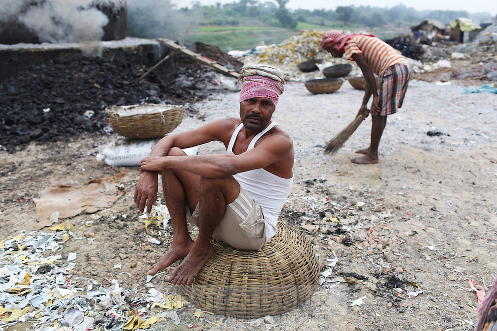 On the outskirts of Kolkata, men carry baskets of leather trimmings to a large cauldron for burning. The small pieces are burnt, dried and then sold for use as fertilizer or as food for farm animals. Burning of the leather produces harmful gases that are released into the air. Workers often have little to no protection.  India. November, 2013