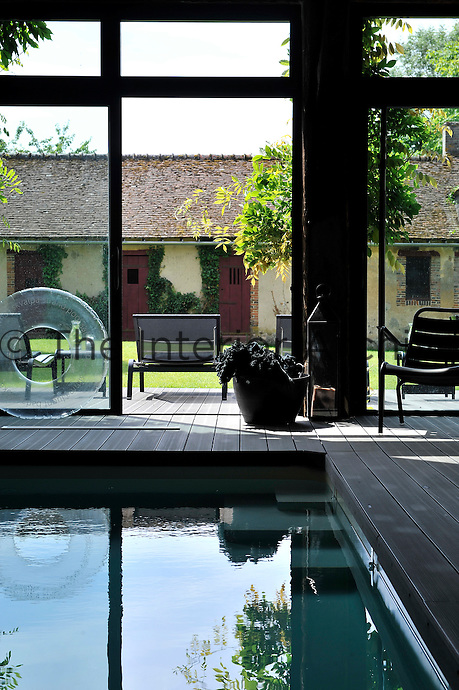 Large glass doors connect the indoor swimiming pool to the garden and the plastic-coated floorboards around the pool have been co-ordinated to match the deck outside