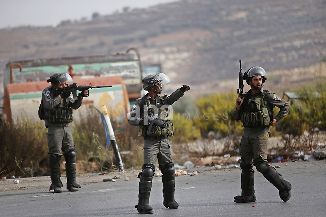 An Israeli soldier aims at Palestinian protester during clashes near the Jewish settlement of Bet El, near the West Bank city of Ramallah, on October 13, 2015. A wave of stabbings that hit Israel, Jerusalem and the West Bank this month along with violent protests in annexed east Jerusalem and the occupied West Bank, has led to warnings that a full-scale Palestinian uprising, or third intifada, could erupt. The unrest has also spread to the Gaza Strip, with clashes along the border in recent days leaving nine Palestinians dead from Israeli fire. Photo by Shadi Hatem