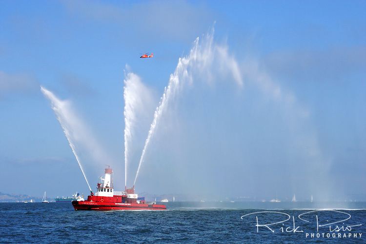 """San Francisco Fire Department's fireboat Guardian No. 2 sprays plumes of water from its nozzles, as a Coast Guard Dolphin helicopter passes overhead, during the 2009 San Francisco Fleet Week Parade of Ships. The Guardian was a gift from the survivors of the Loma Prieta Earthquake to supplement the city's other fireboat """"Phoenix."""""""