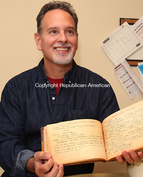 NAUGATUCK CT. 26 October 2015-102615SV04-Michael Bonnardi of Naugatuck works in the kitchen of his home in Naugatuck Monday. Bonnardi wrote two books that honor and preserve the memories and recipes of the early 20th century &ndash; namely the 1930's &amp; 40's. He is holding the recipe book he found from his grandparents.<br /> Steven Valenti Republican-American