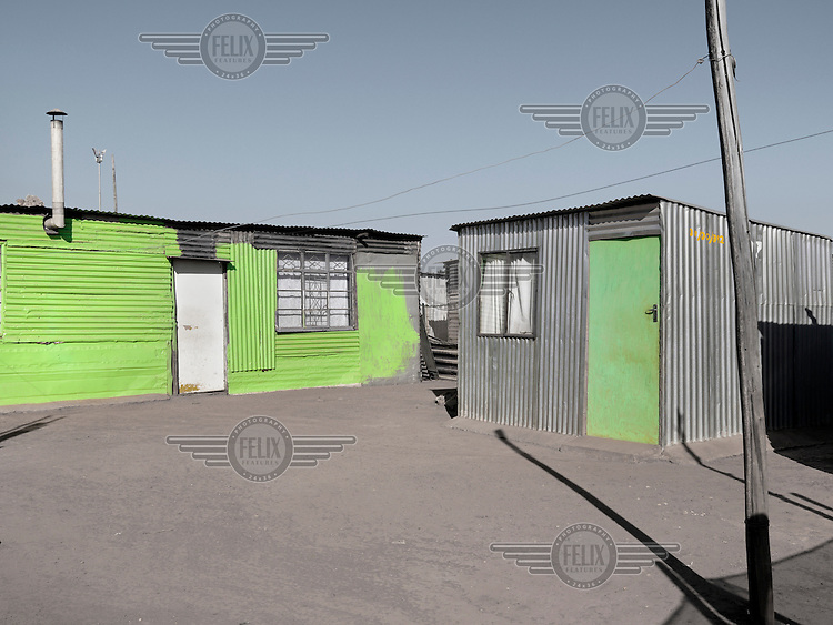 Neat corrugated iron shacks that have been partially painted green.  Graeme Williams' pictures of the environments occupied by some of South Africa's poorest people focus on the interiors and exteriors of people's homes, accentuating the minutiae of the occupants' day-to-day dwelling places. The bright colours captured in these photographs are suggestive of resilience, hope and a sense of humanity that survives in these poverty-stricken communities...