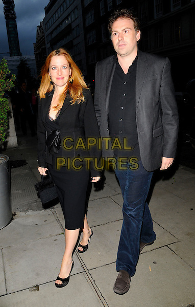 """GILLIAN ANDERSON & GUEST.Attending """"The Return of The Salon"""" Party at the Sanderson Hotel, London, England, UK, May 28th 2008..full length  black jacket  bow tied dress peep toe shoes .CAP/CAN.©Can Nguyen/Capital Pictures"""