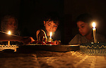 Palestinian family use a candle light as they eat dinner during a power cut in Rafah in the southern Gaza Strip, on July 28, 2015. Independent Commission for Human Rights warned Saturday of the aggravated humanitarian situation in Gaza due to continued electricity outage after the Gaza's sole power plant stopped running, which make problems with water supply because many of the area's water pumps also rely on that power plant. Photo by Abed Rahim Khatib
