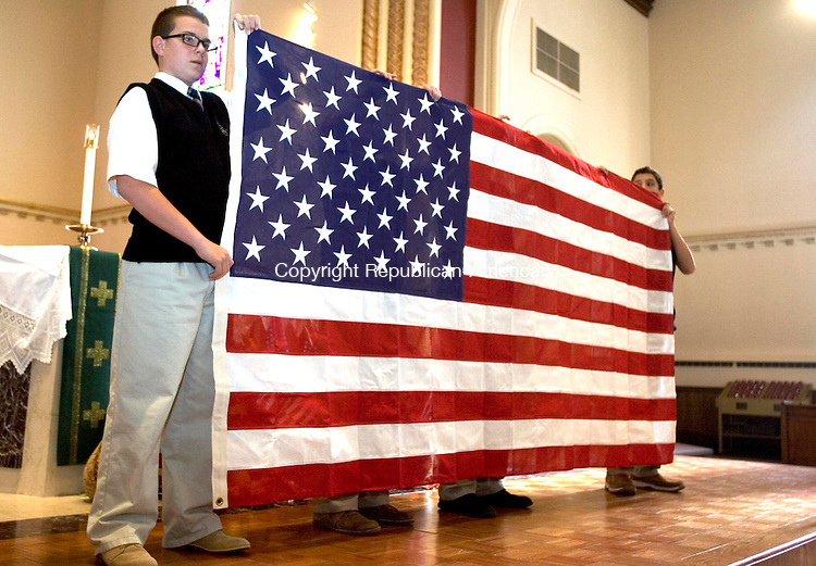 WATERBURY CT. 08 November 2013-110813SV06-Noah Fitzgerald, 13, of Waterbury, left, and fellow students from Our Lady of Mount Carmel School present the history of the American Flag during a mass honoring veterans and current service members at Our Lady of Mount Carmel in Waterbury Friday. <br /> Steven Valenti Republican-American