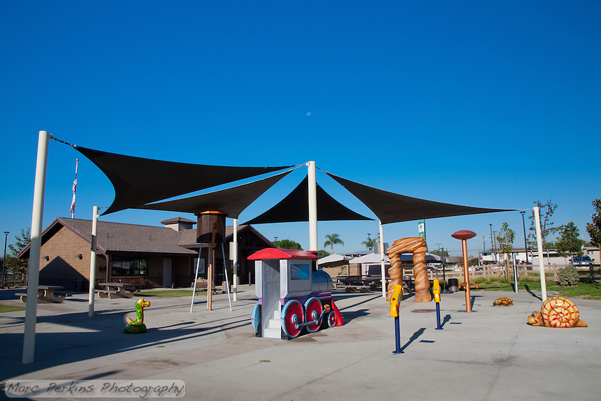 The Splash Pad at Stanton Central Park, seen when the water has been turned off on a sunny day with clear blue sky (and a roughly 3/4 moon in the sky above it).  The shade structures, train that can be climbed through, water tower, and animals are all clearly visible.
