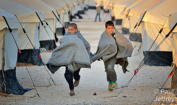 Early in the morning, boys run amid the tents in the Zaatari Refugee Camp, located near Mafraq, Jordan. Opened in July, 2012, the camp holds upwards of 50,000 refugees from the civil war inside Syria, but its numbers are growing. International Orthodox Christian Charities and other members of the ACT Alliance are active in the camp providing essential items and services.