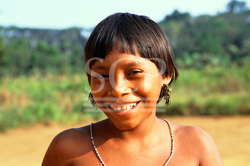 Roraima, Brazil. Smiling Yanomami girl with bead necklace and aromatic leaf deorations in her ears.
