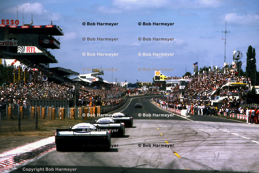 LE MANS, FRANCE - JUNE 20: The winning Porsche 956 002 driven by Jacky Ickx and Derek Bell leads the other two Rothmans Porsche team cars past the pit lane near the finish of the 1982 24 Hours of Le Mans on June 20, 1982, at Circuit de la Sarthe in Le Mans, France.