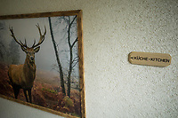Switzerland. Canton Graubünden. Davos. Hotel. A sign on the wall with the words Küche and Kitchen. A painting with a deer in the forest. Deer are the hoofed ruminant mammals forming the family Cervidae. Female reindeer, and male deer of all species, grow and shed new antlers each year.11.07.2020 © 2020 Didier Ruef