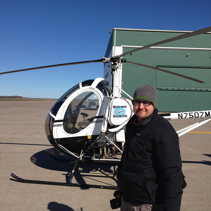 Aaron Peterson with helicopter while on assignment.