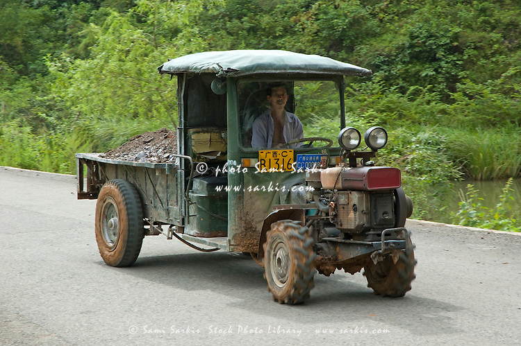 Man riding a tractor on a country road, Yangshuo, Guangxi, China.