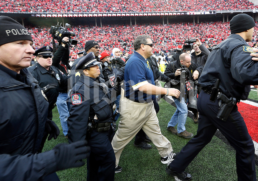 Michigan Wolverines head coach Brady Hoke is escorted off the field by police following the NCAA football game against the Ohio State Buckeyes at Ohio Stadium on Nov. 29, 2014. The Buckeyes won 42-28. (Adam Cairns / The Columbus Dispatch)