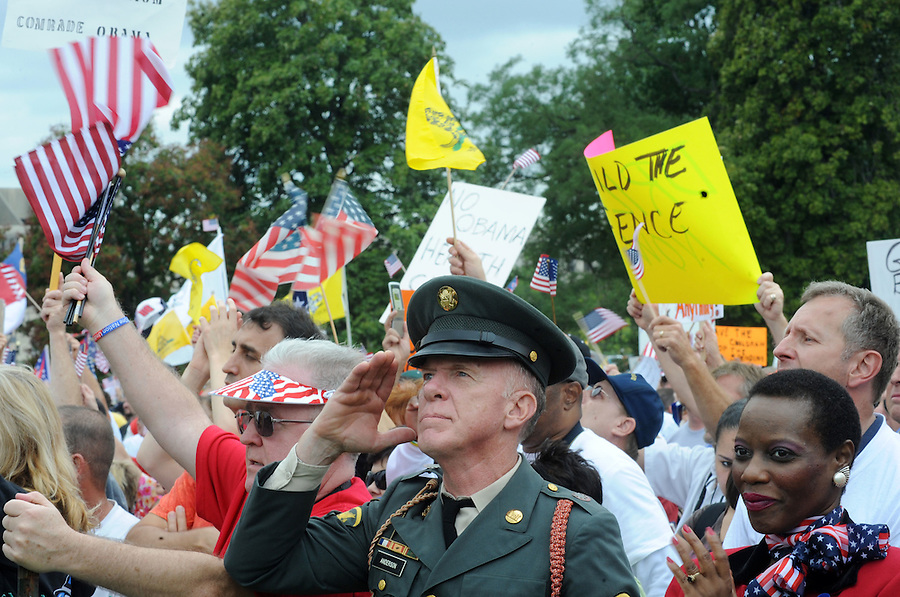 "(center) Steve Anderson, 61, of Sidney, NY, salutes the flag at the U.S. Capitol as (right) Sakina Mengle, of Rockville, MD., looks on during the Tea Party Protest on Sept. 12, 2009 in Washington, DC. He was a Combat Engineer in Vietnam. Anderson said, ""I have a 60 ft. flag that I don't fly in defiance of the most unpatriotic, un-American president we ever had in the history of this nation."""