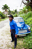 "JAMAICA, Port Antonio. Joseph ""Powder"" Bennett of the Mento band, The Jolly Boys standing in front of a vintage blue car."