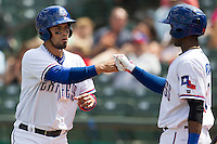 Round Rock Express designated hitter Robinson Chirinos #14 is greeted by teammate Jurickson Profar after he scored against the New Orleans Zephyrs in the Pacific Coast League baseball game on April 21, 2013 at the Dell Diamond in Round Rock, Texas. Round Rock defeated New Orleans 7-1. (Andrew Woolley/Four Seam Images).