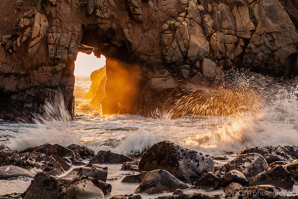 Splashing waves at sunset through the arch at Pfeiffer State Beach in Big Sur California