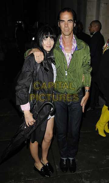 "GUEST & NICK CAVE .At the ""Daydreaming with...James Lavelle"" exhibition private view, Haunch of Venison gallery, London, England, UK, August 26th 2010..full length green jacket arm around jeans black umbrella .CAP/CAN.©Can Nguyen/Capital Pictures."