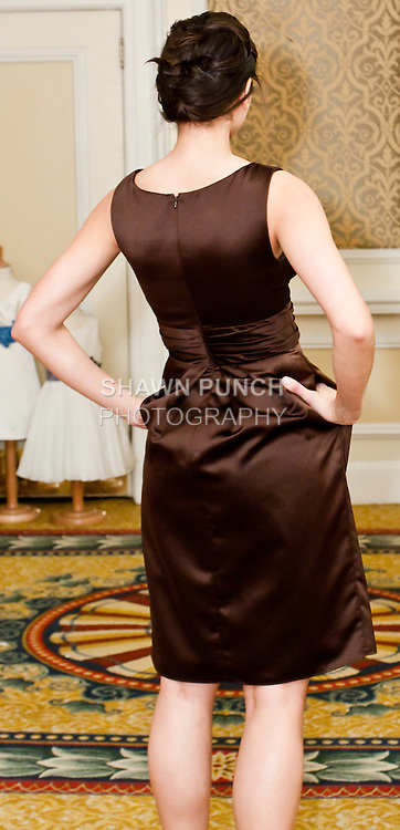 Model walks in a mahogany soft satin v-neck dress with tucked empire band and slim, knee length skirt, by from the Watters Fall 2010 Bridal Collection, during the Wedding Channel Couture Show Fall 2010.