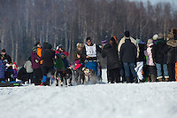 John Baker weaves his team through fans on Long Lake during the restart in Willow of the Iditarod sled dog race Sunday, March 3, 2013.