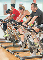 NWA Democrat-Gazette/BEN GOFF @NWABENGOFF<br /> Joseph Bartlett (from right) of Rogers, Kayla Bruskas of Fayetteville and Carl Lanje of Springdale push through the final minutes of the bike segment Saturday, March 10, 2018, while competing in the 2018 Indoor Triathlon at the Jones Center in Springdale. Participants started in waves and had 10 minutes to swim, 20 minutes on a stationary bike and 15 minutes on a treadmill to log as many miles as possible.