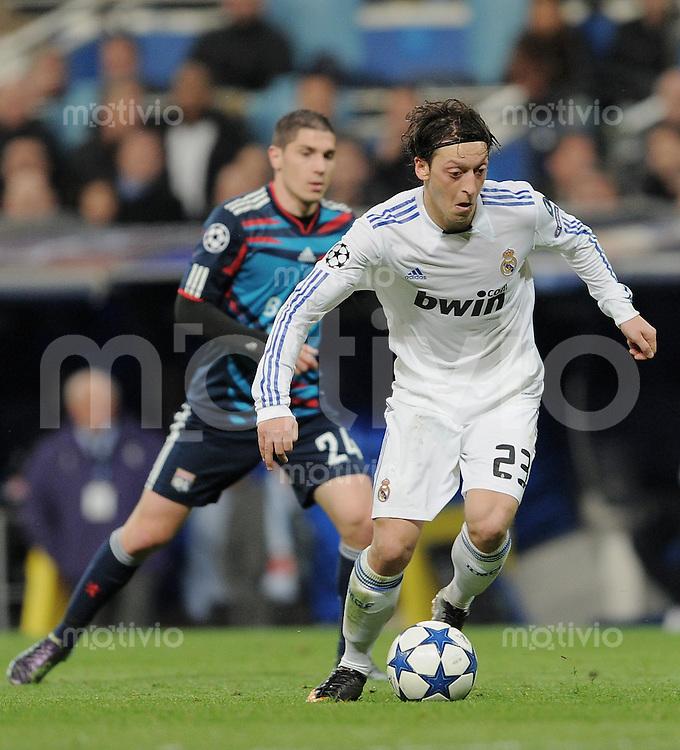FUSSBALL   CHAMPIONS LEAGUE   SAISON 2010/2011   Achtelfinale  16.03.2011 Real Madrid  -  Olympic Lyon  Mesut Oezil (Real Madrid) mit Ball und Jeremy Pied (hinten, Lyon)