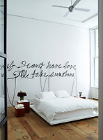 """The bedroom is as ascetic as a monk's cave with white walls, white sheets on the Corian platform bed, minimal furniture and unpolished wood floors save for the arresting artwork hanging on the wall. The piece, a neon wall sculpture by Glenn Ligon, spells out the phrase, """"If I can't have love I'll take sunshine"""" in cursive scrawl. The circa 1960 bedside tables are by Joseph-André Motte and the walls are sheathed in a Marmorino wall finish."""
