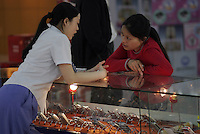 A young woman shops for a mobile phone at an electronics store in Shanghai, China..