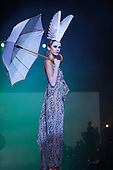 Model posing on catwalk with original paper hat and umbrella